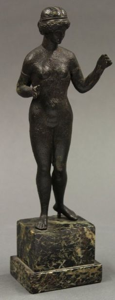 Bronze of Clotho with thread, possibly Greco-Roman. Clotho, one of the three Fates, is depicted as a nude holding a ribbon or 'thread' in one hand. Her arms are spread as if to measure the ribbon.