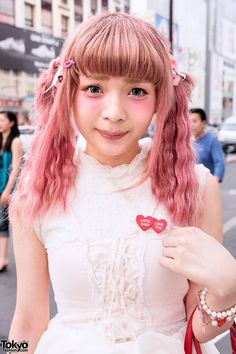 Aug 2014: Eri's look features a pink Swankiss corset over a white Swankiss dress, over-the-knee stockings, and Tokyo Bopper platform shoes. Accessories include SPANK! hair ties, a stretched ear, Katie heart badges, and a candy red heart-shaped purse from RNA.