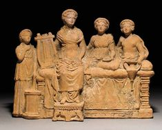 Greek terracotta group, Hellenistic period,  2nd century B.C.   With two reclining female figures, a seated lyre player and a standing girl, with pillows below their elbows, holding a two handled vessel in her left hand, a girl standing to the left, wearing a chiton, her right arm to her chest and her left arm lowered, resting on trumpet supported by a cylindrical drum, each figure with center parted wavy hair beneath thick fillets, 23.1 cm long. Private collection