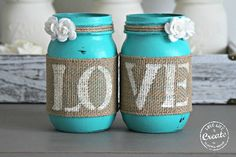 Two decorative Mason Jars in Turquoise . Each jar is hand painted & distressed, decorated with natural burlap with old white letters spelling LOVE. and two paper, off white roses. SIZE: REGULAR MOUTH