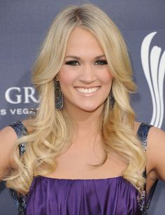 A trick to keeping strands from looking limp is layers. Carrie Underwood always has long layers throughout her hair to beef it up. We also love her soft side bangs that compliment her long face.