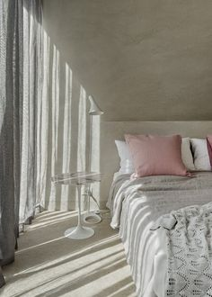 a touch of soft pink in a white/grey bedroom makes it romantic