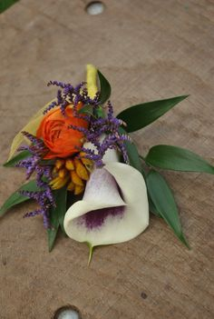 cluster style buttonhole of a two tone purple and cream calla lily, orange ranunculus, lilac limonium, gold kangaroo paw and soft ruscus foliage, detail of yellow organza ribbon