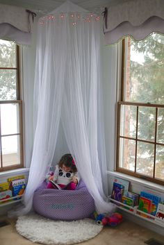 Princess Reading Nook… IKEA spice racks for books, Bed Bath & Beyond hoop bed canopy and Pottery Barn Kids Beanbag.