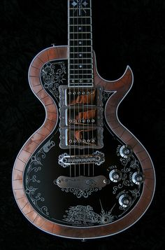La Morena E Series:   Features hand-inlaid copper outline, a black anodized and engraved front plate, and chrome plated hardware. The rear is finished in the same rich color as the La Canastera and La Llama guitars. This complements the look of the natural copper really well.