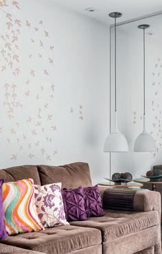 Almofadas + adesivos: o sofá revestido de camurça cor de café teve a sisudez quebrada pelas almofadas com diferentes estampas coloridas. Atrás dele, delicadas folhas secas ao vento decoram a parede. No canto, diante do espelho, a mesa lateral recebe o facho de luz do pendente branco – fixada a 80 cm do teto, a peça usa lâmpada incandescente leitosa, que proporciona uma atmosfera para lá de aconchegante.