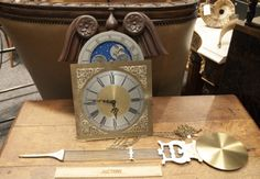 VINTAGE WEST GERMANY MOON PHASE CLOCK WITH PENDULUM AND CHAINS. JUST NEEDS A NICE TALL WALL OR GRANDFATHER CASE TO PUT INSIDE. COMES WITH CARVED FINIAL TOP PIECE.