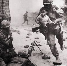 This image shows an American soldier risking his life to save two Vietnamese children during a fight. This is bravery.