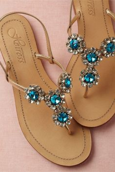 Radiant blue flowers on a simple sandal silhouette beg to walk the sands of faraway shores. From Heiress. Buckle closure. Leather and glass upper, leather sole. Handmade in India.