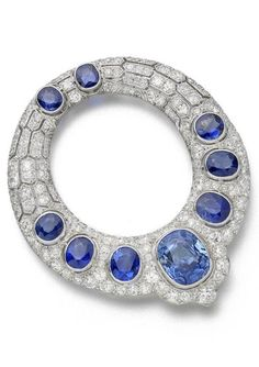 An Art Deco sapphire and diamond brooch, circa 1935. The annular plaque collet-set with graduating cushion-shaped and circular-cut sapphires on a pavé-set old brilliant, brilliant and single-cut diamond ground with elongated hexagonal pierced detail, mounted in white gold and platinum, French marks, later fitting, diameter 5.8cm. #ArtDeco #brooch