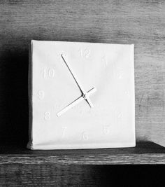 Embroidered clock. The hours are fixed, embroidered on a white cotton sheet to cover the mechanics of the clock. This clock, with a soul of solid wood, can be placed on a table or hang on a wall according to the wood. (photo by J. Oppenheim)