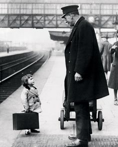 a very young passenger asks a station attendant for directions, on the railway platform at bristol,england, 1936.photo bygeorge w. hales.