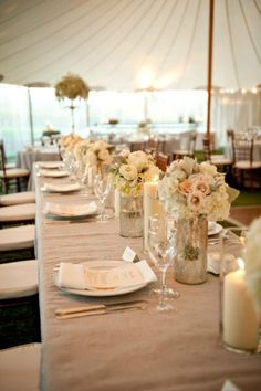 I like this idea for the head table, lots of the smaller centerpieces and maybe do one or two large ones either on the ends or one in the center and use the antique silver mercury glasses and add some floating candles