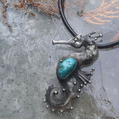The handmade necklace is made of tin and turquoise The dimensions of the pendant are 40 mm x 75 mm. The jewel is hung on a 18 inches long leather cord .