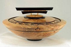 """I haven't been turning for awhile and decided I'd better do something before I forget how to do it.  This piece is turned from figured Maple and Ebony. It measures 13"""" X 6"""". The design in the ring around the top was defined using pyrography and then pierced.  Comments and suggestions are always welcome."""