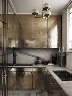 Dans la cuisine, des panneaux en argent massif martelé reflètent la lumière diffusée par le lustre en bronze Stilnovo vintage (Galerie Alexandre Goult).