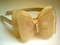 Tiara infantil laço, confeccionada em organza cor dourada com acabamento em strass.