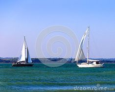 A pair of  yachts sailing on a calm sea in West Wittering in Sussex.