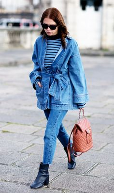 A denim wrap jacket is worn with light wash jeans, a striped top, and black ankle boots.