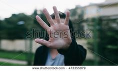 Man hiding the face with his hand standing outdoor