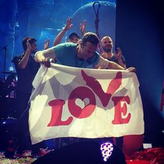 As seen in use by Coldplays' Chris Martin, the official Love Button Global Movement Love Flag with our original red Logo is here for your to show your Love. Coldplay Tour, Coldplay Concert, Coldplay Lyrics, Chris Martin Coldplay, Phil Harvey, Jonny Buckland, British Rock, Britpop, Best Fan
