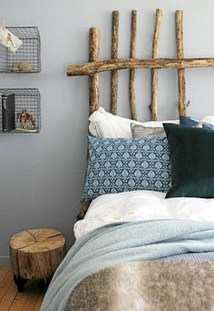 Headboard made of branches - the tree trunk piece and colors here make the headboard look like it belongs