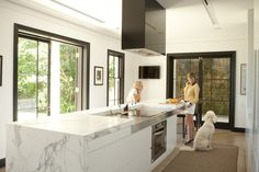 Kitchen in stainless steel and Calacutta marble with black mirror wrapped rangehood. Brooke Aitken Design.