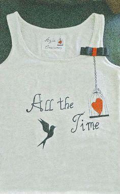 Camiseta de tirantes en color gris jaspeado. Modelo All the time. Broche de lazo bicolor en rojo y negro (opcional). Precio 20 €.