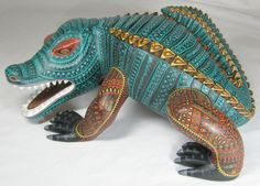 Unique crocodile from Jacobo Angeles. This one-piece-of-wood carving has been cut with a rough, corrugated, ripple-like skin. Highly creative idea, with elaborate Zapotec motifs covering the hide.