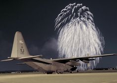 Fireworks erupt in front of a C 130 Hercules on the flightline at Yokota Air Base Japan at the Independence Day festivities