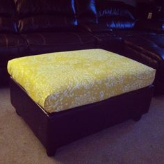 Ottoman recover DIY using an old duvet cover, glue gun, and safety pins! Yellow and cream pattern with brown leather base.