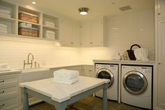 Clean white laundry room, marble topped folding table...