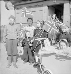 Norwegian children waive the Norwegian flag and greet Allied forces at Gardermoen airfield near Oslo after the capitulation of German forces and the liberation of Norway.