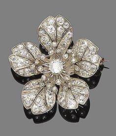 A diamond flower brooch, circa 1890  Realistically modelled as a hibiscus flowerhead, centrally-set with an old brilliant-cut diamond stamen within a rose-cut diamond surround, to cushion-shaped, single and rose-cut diamond petals with veining details, mounted in silver and gold, old brilliant, single-cut and cushion-shaped diamonds approx. 4.40cts total, detachable brooch fitting, length 4.2cm