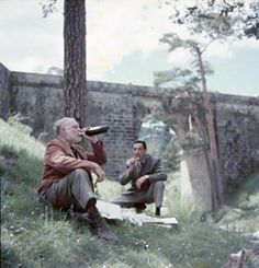 EHC-379T Ernest Hemingway drinking from a bottle of wine and Adamo Simon (chauffeur) eating by a bridge and a river with the newspaper on the ground in Spain.