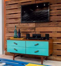 Feito com quatro paletes, o painel suspende a TV e ainda esconde a fiação, amarrada atrás de uma das pranchas verticais.