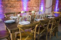 Rustic Garden Wedding Reception Table Decor with Farmhouse Table, Wooden Chairs, and Ivory and Purple Floral Centerpieces | Tampa Wedding Chair Rentals A Chair Affair | Tampa Wedding Venue CL Space