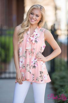 This peach blouse will be a perfect addition to your wardrobe! It features a gorgeous floral pattern in white, beige, and hot pink on a peach fabric. It's sleeveless, has slightly textured fabric, and has pleated front and back panels. We love the cute fabric tie around the collar, as well!
