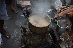 A tea cooker's (chai walla's) pot cooking spiced tea (masala chai) on a coal fire in a street of Kolkata