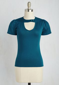 After a long day of editing at the zine, you strut off to happy hour, dressed for the occasion in this blue-green top. Dolled up with a buttoned strap atop its V-neck, you toast with your coworkers in perfectly retro elegance!