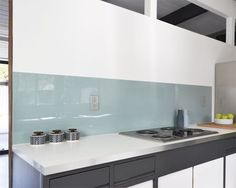 Instead of heavy glass, the homeowners installed lightweight painted acrylic as the backsplash.