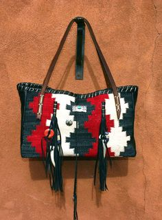 Navajo Handbags made from blankets / rugs, vintage horse tack, and deer, elk or cowhide leathers. I embellish the bags with vintage trade beads, turquoise, coral, nickel silver/German silver Concho buttons, nickel silver spots/studs, and deer antler tips  Ooo So Santa Fe