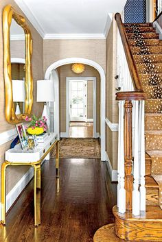 Aesthetic Oiseau: Traditional Twist in Richmond, Designed by Charlotte Lucas, Photos by Laurey Glenn for Southern Living, brass and lacquer console, hall, foyer, entry, arch entry, gold mirror, antelope rug stain runner, grasscloth wallpaper, wood floors, wood stairs