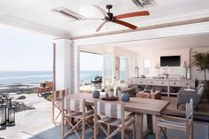 Chic covered patio features a ceiling fan over an outdoor trestle dining table lined with gray striped director's dining chairs overlooking the ocean.