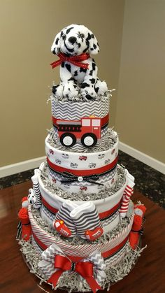 """""""Little hero"""" firetruck theme diaper cake. 4 tiers, 4 receiving blankets,  6 washcloths, 3 pair of rattle socks, and 75 Huggies diapers.  More pics on my Facebook page Simply Showers. https://m.facebook.com/adorablegifts"""