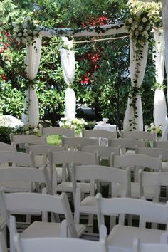 A backyard chuppah with flowers and birch tree poles