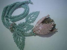 Colar confeccionado com miçangas,vidrilhos e perola, utilizando a tecnica de entrelaçamento (beadwork), nas cores rosa, verde e marrom . Comprimento do cordão com a flor = 32cm ( flor=5cm ) Comprimento do cordão com folhas = 38 cm ( folhas=7cm )