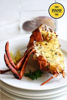 Halve the lobster and crack the claws. Remove the gills. the green sac behind the head and the black vein running down the body. Place...