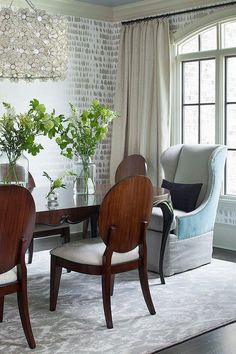 Chic dining room features walls clad in gray print wallpaper, Schumacher Queen of Spain Wallpaper, surrounding a classic dining table and chairs as well as gray and turquoise blue wingback chairs placed at each end of the table atop a gray damask rug lit by a Capiz Flower Drum Pendant.