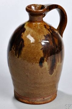 Skinner's - The Personal Collection of Lewis Scranton, Auction 2897M. May 21, 2016. Lot: 151.  Estimate: $400-600.  Realized: $1,400.   Description:  Redware Jug, Alfred, Maine, early 19th century, flared rim and applied strap handle on tall slightly ovoid body with manganese decoration, ht. 6 1/2 in.   Provenance: Hilary Nolan, 1990.